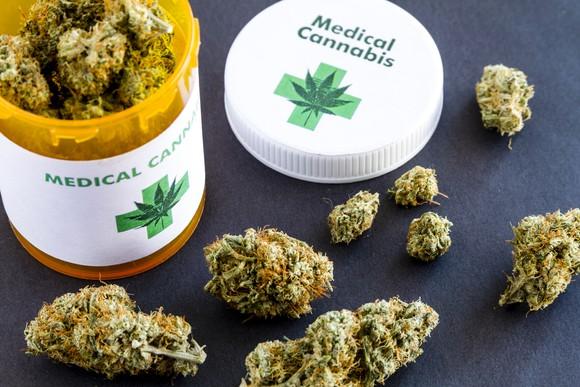 Marijuana buds rest on a table beside an open prescription bottle.