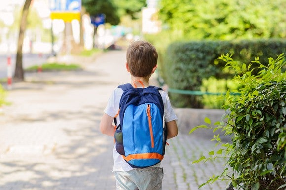 A child with a backpack, walking away on the sidewalk.