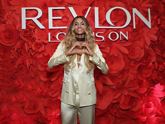 The singer Ciara standing in front of a heart made of flowers and a Revlon sign