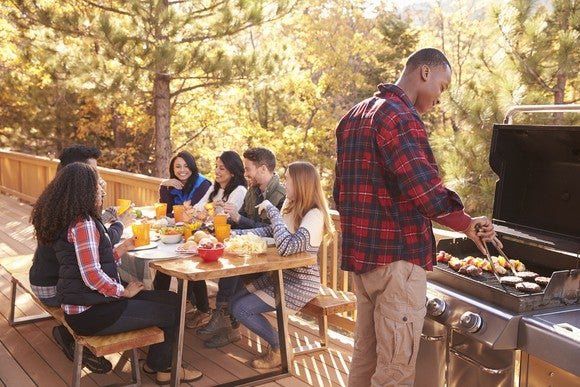 Friends gather for a cookout on a deck.