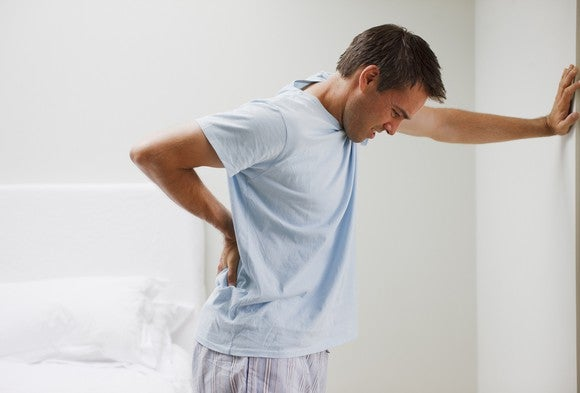A man leans against a wall holding his back in pain.
