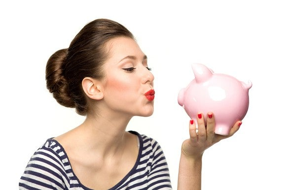 A woman puckers up for a piggy bank in her hand.