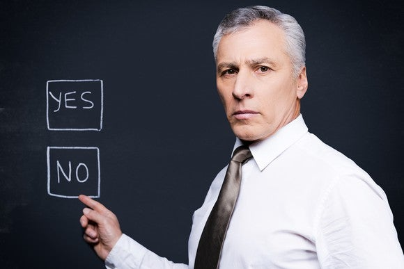 "A pre-retiree pointing to a ""No"" answer key on a chalkboard."