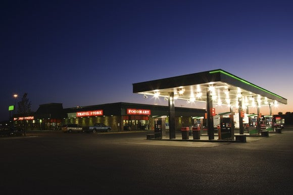 An exterior view of a gas station at night.