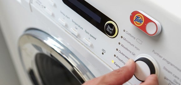 An Amazon Dash button for Tide sits on a washing machine.