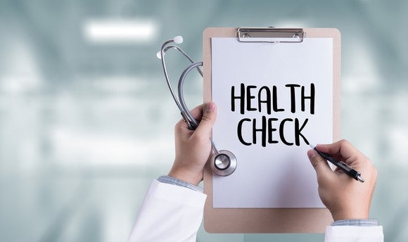 "Two white-sleeved arms, holding a stethoscope, a pen, and a paper reads ""health check"" attached to a clipboard."