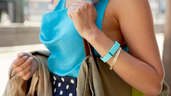 A woman wearing a Fitbit bracelet.