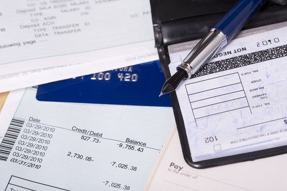 A statement showing negative net worth, mixed in with a credit card, pen, and check register.