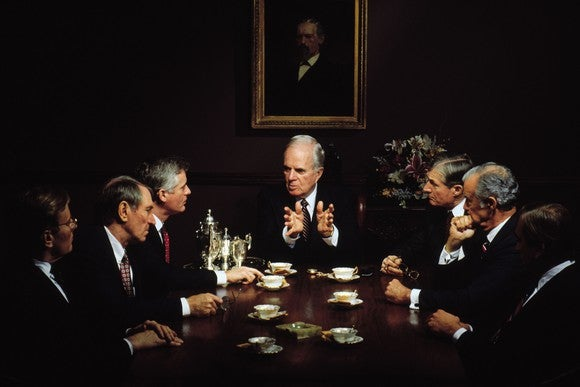 Executives sit around a conference table in board meeting
