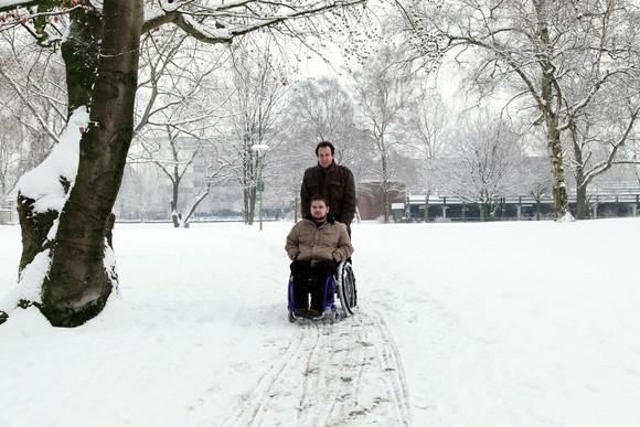 A man pushes a boy in a wheelchair through the snow.