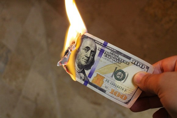 A hand holds a burning $100 bill.