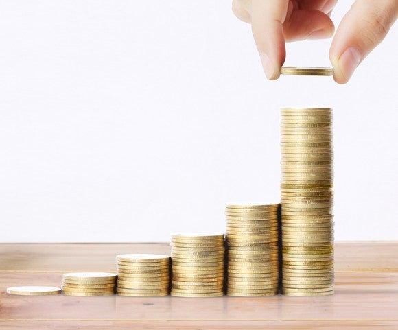 A person stacks piles of coins in increasingly ascending heights, suggesting the positive wealth creation that can come from investing in dividend stocks.