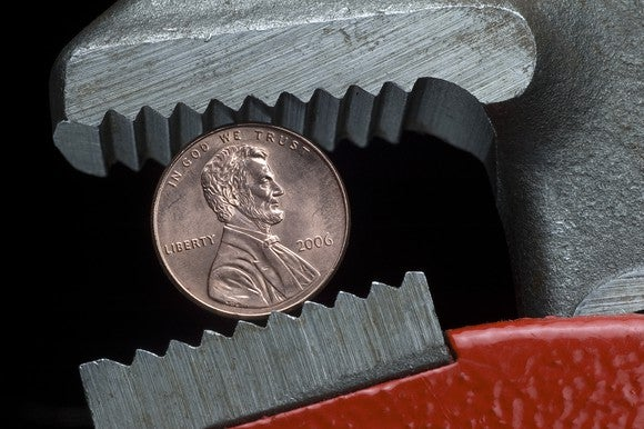 A penny being held in a wrench.