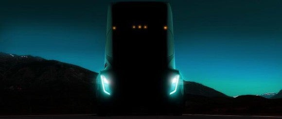 The front of a Tesla Semi with its lights on.