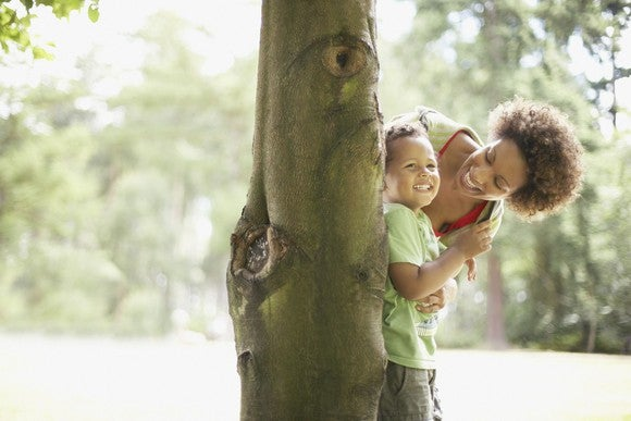 Mother playing hide in seek with son in park