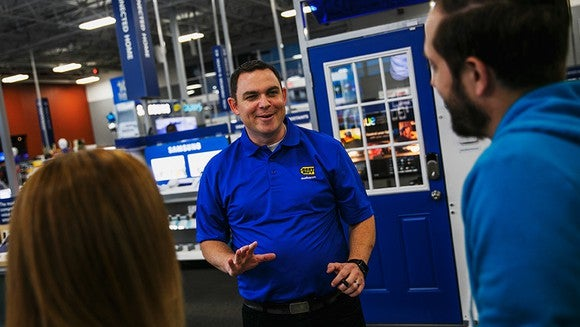 A Best Buy customer service person assisting two customers.