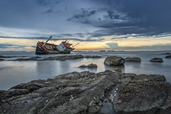 Cargo ship on rocks.