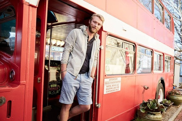 A man stands in the doorway of a bus wearing fashionable Abercrombie clothing.