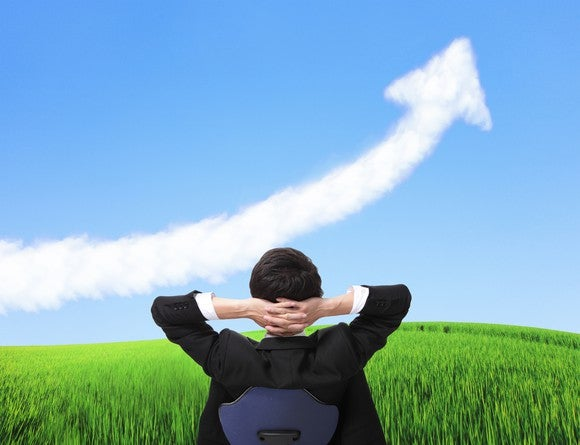 A person in a business suit looks at a cloud shaped like an upward-sloping arrow.