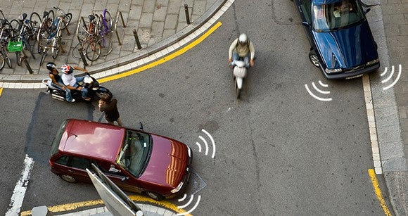 Cars and motorcycles navigate an intersection, with illustrations suggesting image sensors on the cars.