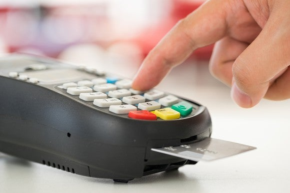 A hand hovers over a credit card machine, with a card inserted into the chip reader.