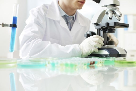 A biotech lab researcher using a microscope.