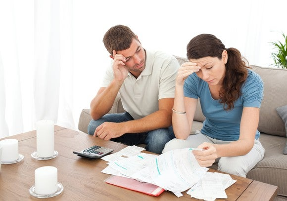 A couple sits at a table, reviewing their pile of bills and looking stressed.