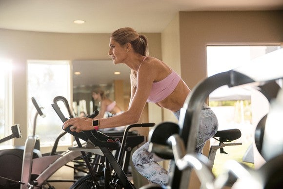Gabby Reece sports a Fitbit while using a stationary bicycle.