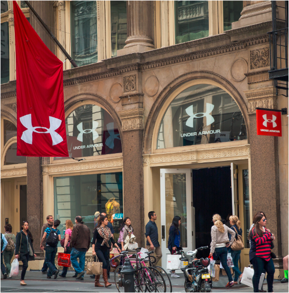 Under Armour's New York Soho district store with lots of people with shopping bags walking in front of the store.