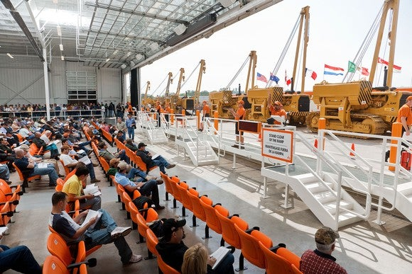 Auction site with a collection of heavy equipment on display and rows of bidders sitting in the audience.