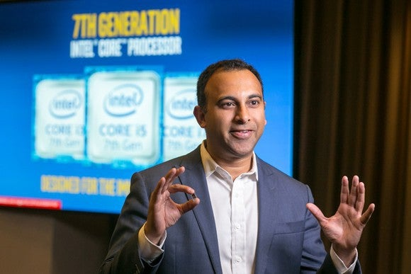 Intel executive Navin Shenoy holding a chip.