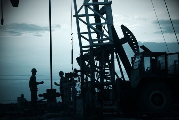 Oil workers on a rig. silhouetted against the sky.