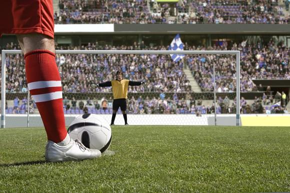 Soccer player waits to kick a penalty kick on goal