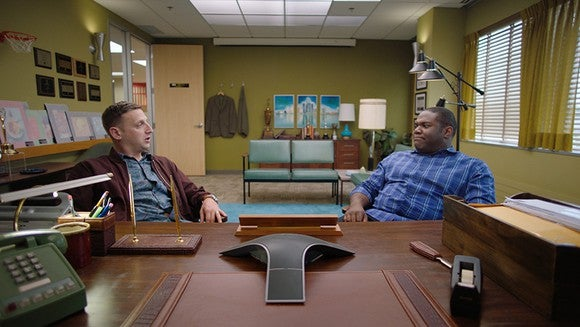 Still from Detroiters: Sam and Tim stare at each other puzzled on the same side of an executive desk.