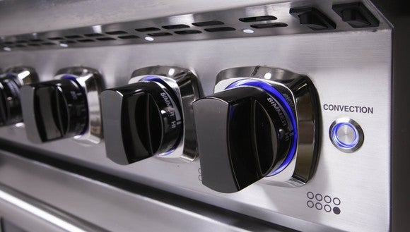 Multiple knobs on a professional stove.