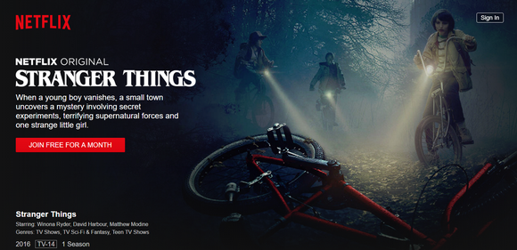 "An ad for Netflix's ""Stranger Things,"" showing three kids on bikes at night, shining a light on a bike on the ground with no rider."