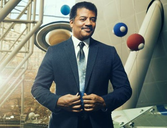 Neil deGrasse Tyson, with a model of planets in the background