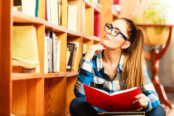 A high school student in a library debating what college she should attend.