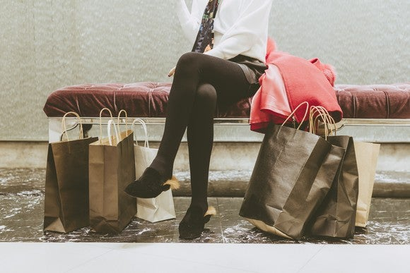 Shopping bags piled at a woman's feet.
