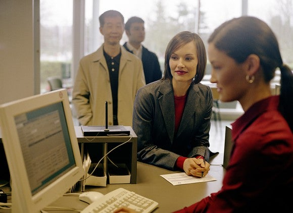A bank teller helping customers.