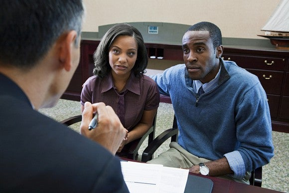 A couple discussing a loan with the manager of a bank.