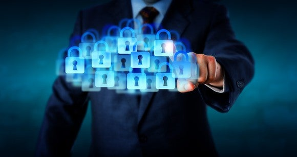 A businessman presses a cloud of digital padlocks.