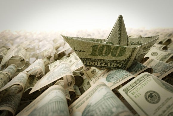 Ship made of money floating on a sea of cash.