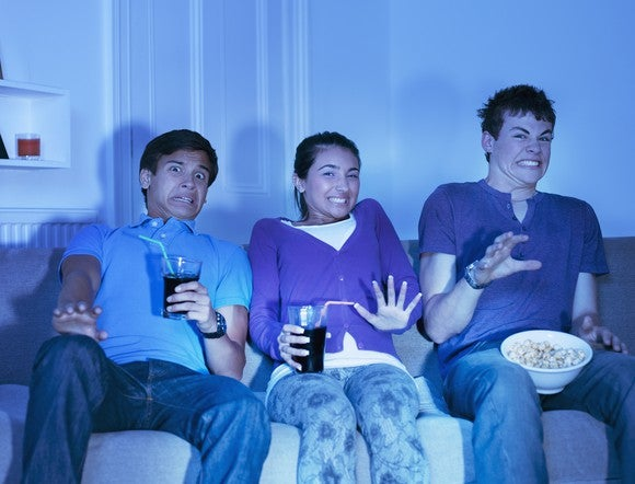 Several teens stream content from the sofa at home.