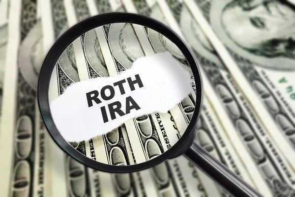 "Magnifying glass over the words ""Roth IRA"" with dollar bills in the background"