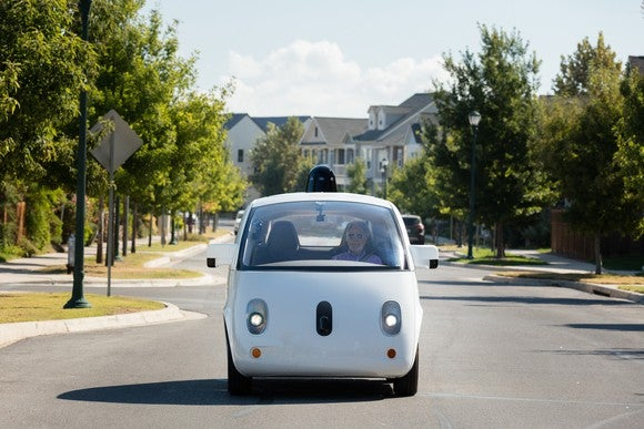One of Alphabet's Waymo self-driving cars drives down a street.