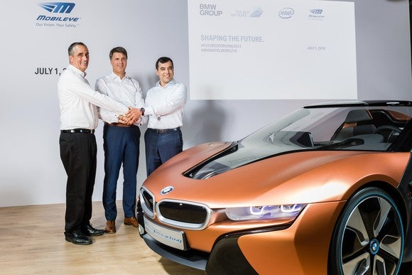The three are shown on a stage with an orange BMW i8 sports car.