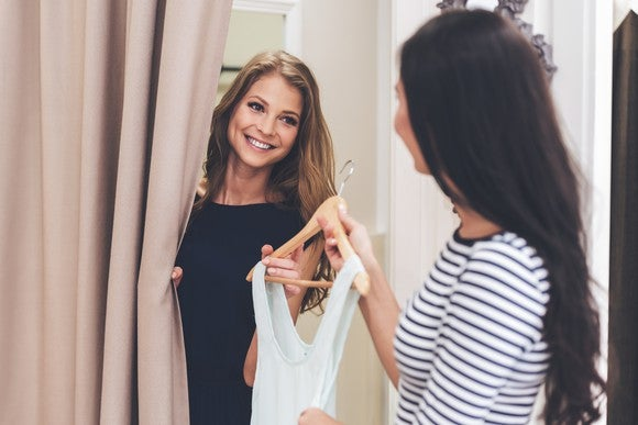 A woman is handed a dress to try on in a dressing room.