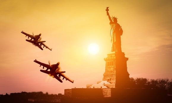 Two fighter jets flying with the Statue of Liberty in the background.