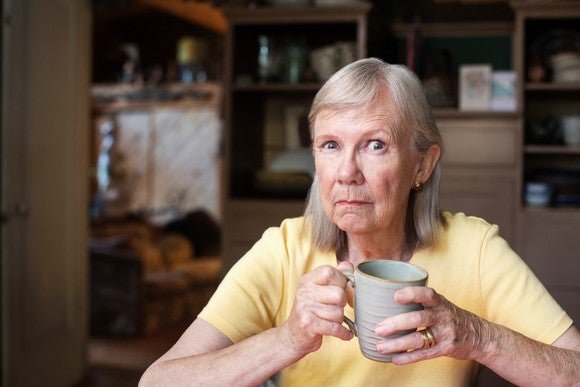 An older woman, clutching a cup in her hands, casts a suspicious look.